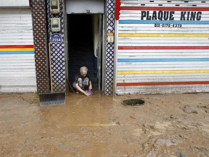 A man scrapes mud off the entrance of his residence in a street covered by mud after heavy rains near the US military base, Camp Casey in Dongducheon, north of Seoul, South Korea.