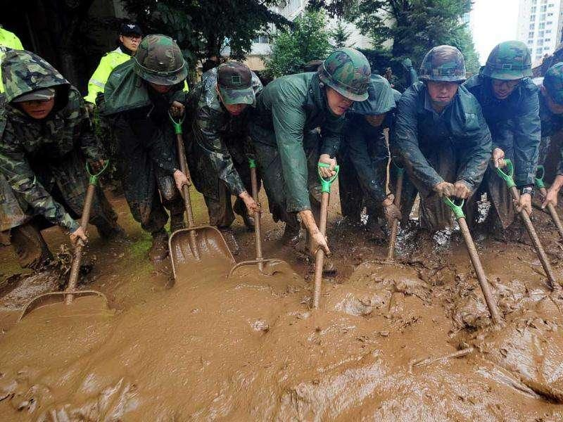 South Korean soldiers shovel tons of mud after a flood caused by heavy rains hit the area around an apartment complex in Seoul.