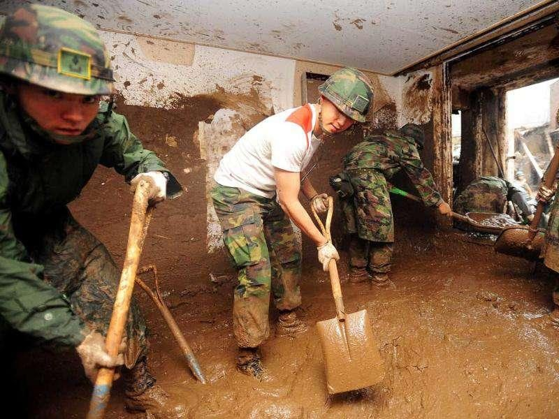 South Korean soldiers remove tons of mud from the inside of a building after a flood caused by heavy rains hit the area around an apartment complex in Seoul.