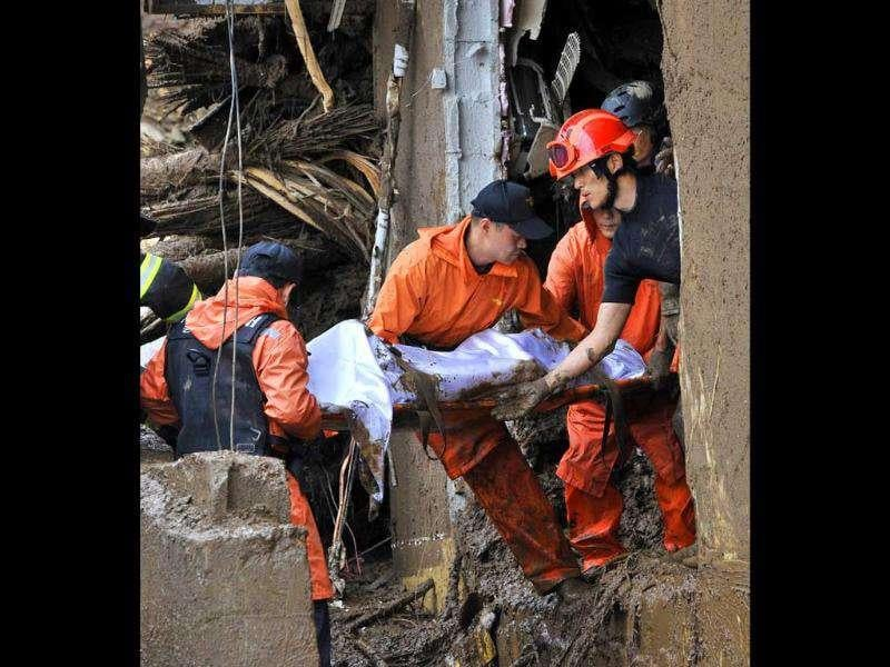 Rescue workers carry a dead body after a landslide hit a small Buddhist temple in Dongducheon, 40 kms north of Seoul.