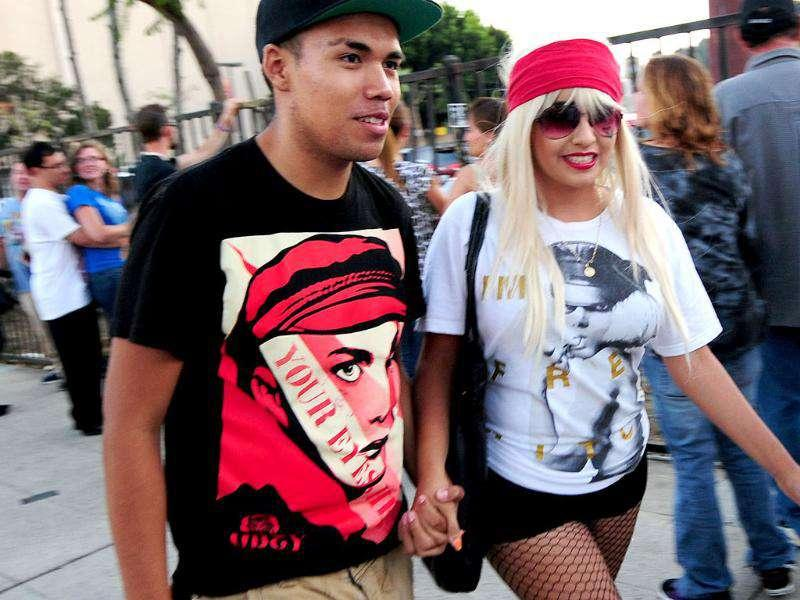 A fan dressed as pop singer Lady Gaga walks hand in hand with her partner along Hawthorne Avenue ahead of a concert by Lady Gaga on an outdoor stage behind the Jimmy Kimmel Live! studio next to the El Capitan Theatre in Hollywood.