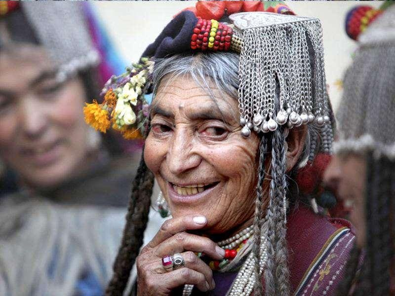 An Aryan Brogpa woman in traditional outfit smiles at Darchik, in Kargil district of Jammu and Kashmir.