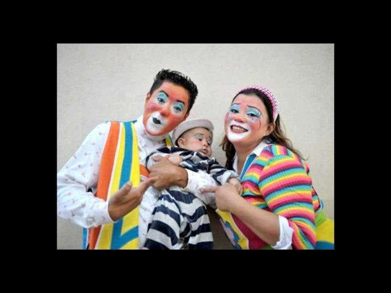 Clown couple pose with their baby for the camera during a parade in the historic centre of Guatemala City in the framework of the III Latin American Clown Congress.