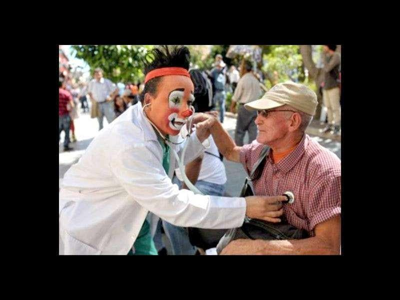 A clown dressed as a doctor examines a man during a parade in the historic centre of Guatemala City in the framework of the III Latin American Clown Congress.