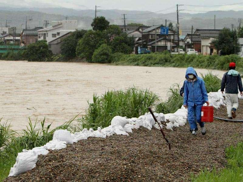 Local residents walk on a bank of the Igarashigawa River swollen with heavy rain in Sanjo, Niigata Prefecture.