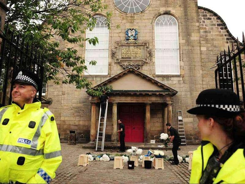 Police oversee the final preparations at the Canongate kirk (church) in Edinburgh ahead of the wedding of equestrian star Zara Phillips.