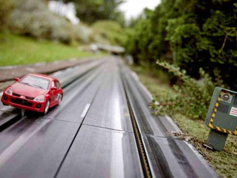 A miniature replica shows a car on a road next to a radar at the 'France Miniature' leisure Park.