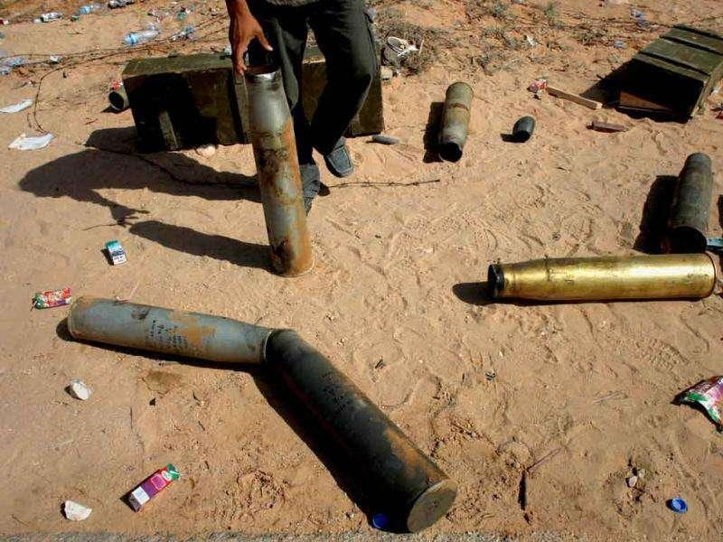 A Libyan rebel stands with spent tank shells after rebels overran a government army position near the village of Hawamid in western Libya