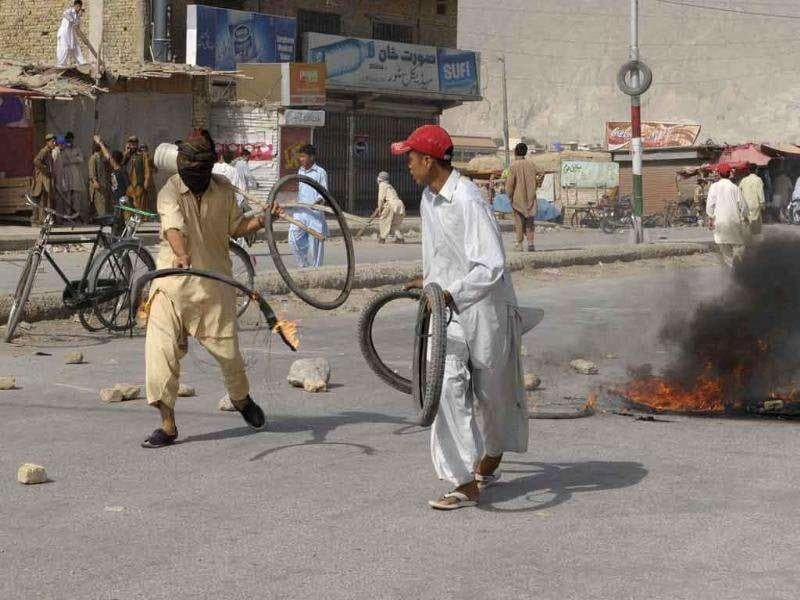 Pakistani Shiites burn tires to protest against the killing of Shiites in Quetta after a passenger van carrying Shiite Muslims was attacked by gunmen.