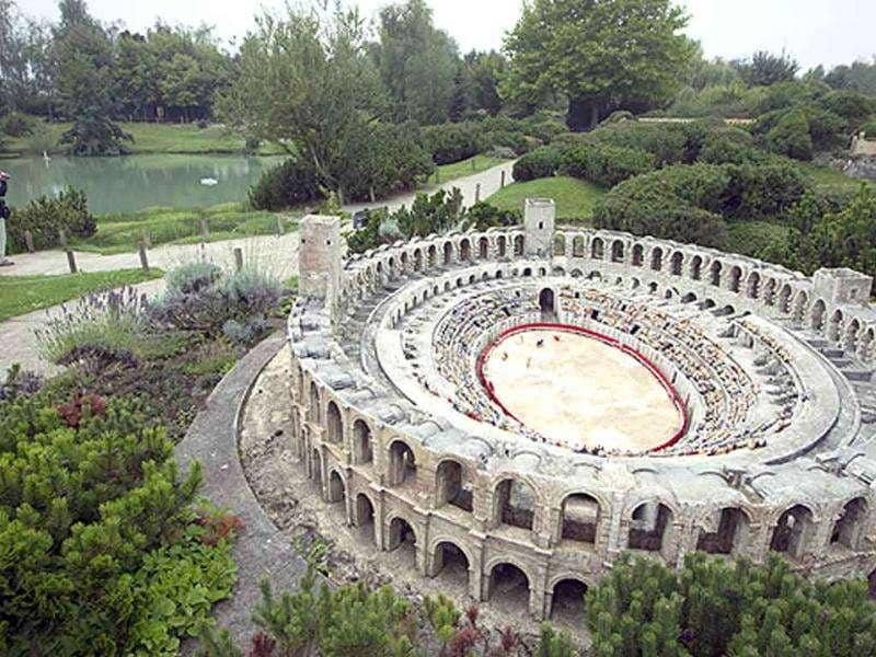 A tourist (L) takes photographs next to a miniature replica of Arles Roman Arena, located in southeastern France, at the 'France Miniature' leisure Park in Elancourt, a western Paris suburb.