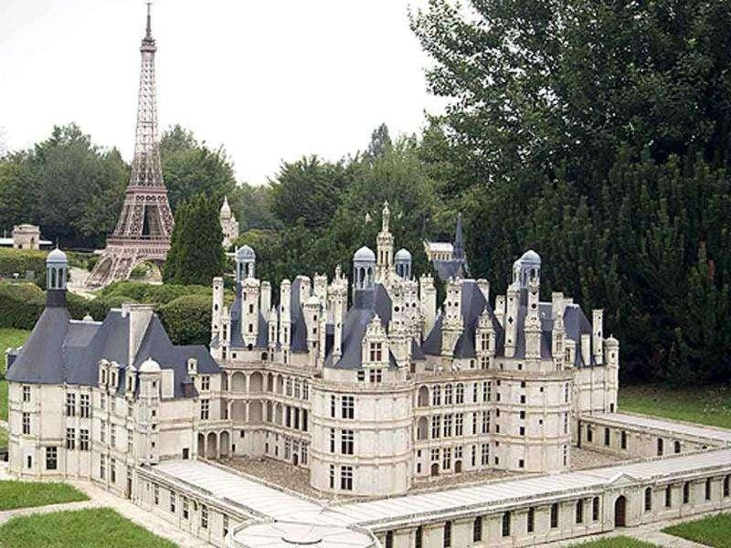 A miniature replica of the Chambord Castle (front), located in the French Loir-et-Cher region, and the Paris Eiffel Tower (back) are pictured at the 'France Miniature' leisure Park in Elancourt, a western Paris suburb.