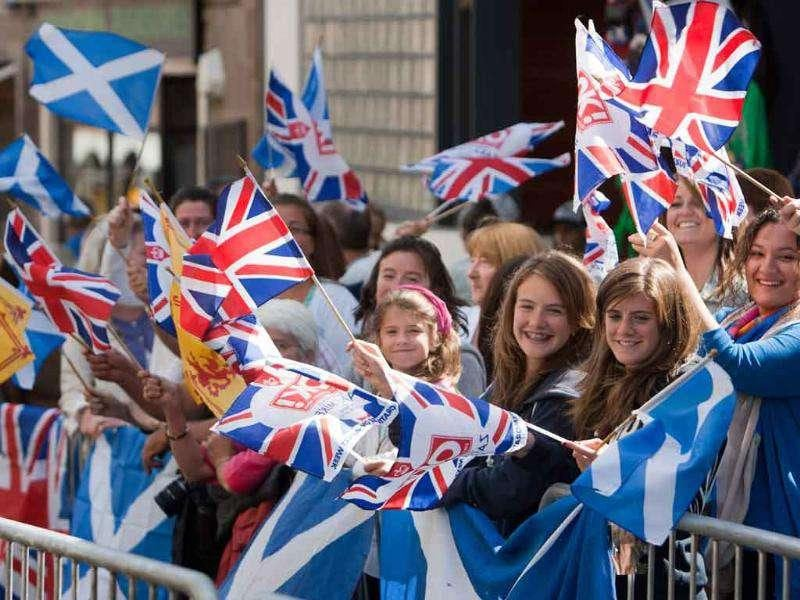 Members of the public wave flags as they wait to see members of Britain's royal family during the wedding of the Queen's grandaughter Zara Phillips and England rugby player Mike Tindall at Canongate church, Edinburgh, Scotland.