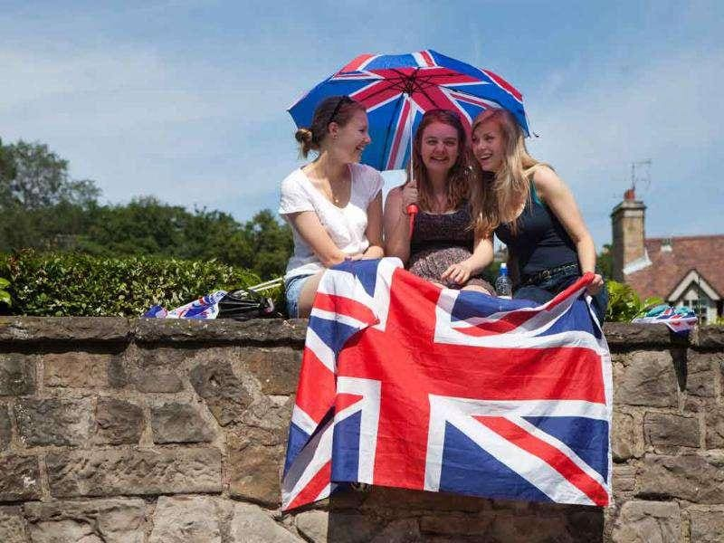 Members of the public sit on a wall as they wait to see members of Britain's royal family during the wedding of the Queen's grandaughter Zara Phillips and England rugby player Mike Tindall at Canongate church, Edinburgh, Scotland.
