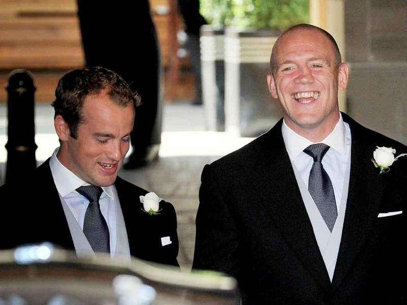 England rugby player Mike Tindall, centre, reacts as the he sees the crowd waiting for him outside his hotel in Edinburgh as he departs for his wedding to Britain's Queen Elizabeth's granddaughter Zara Phillips.