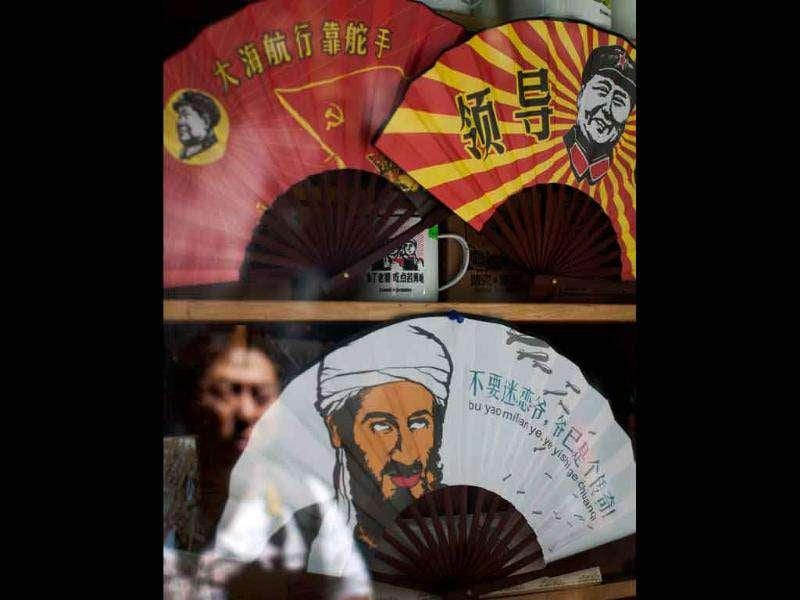 A visitor is reflected on the window of a shop, displaying folding fans with a caricature of Osama bin Laden along with Mao Zedong for sale at a shop in Beijing.