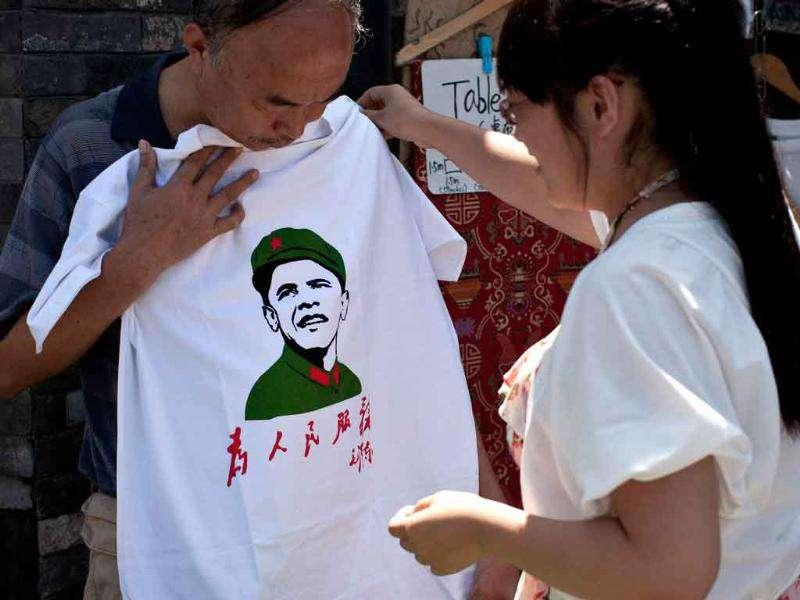 A Chinese woman helps a man as he holds a T-shirts with an image of US President Barack Obama dressed in a Cultural Revolution-era military uniform at a shop in Beijing.