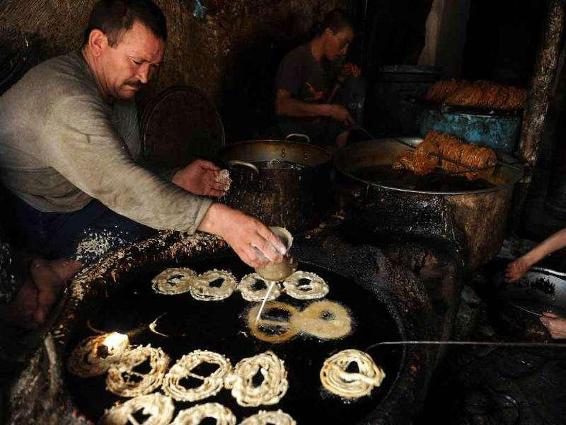 Afghan men make sweets in a shop in Kabul on the eve of the start of the Islamic holy month of Ramadan.