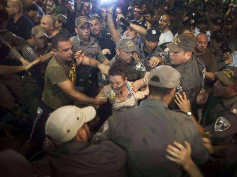 Israeli policemen try to arrest a young woman after protestors blocked a main junction following a protest march against rising housing prices and social inequalities in Tel Aviv.