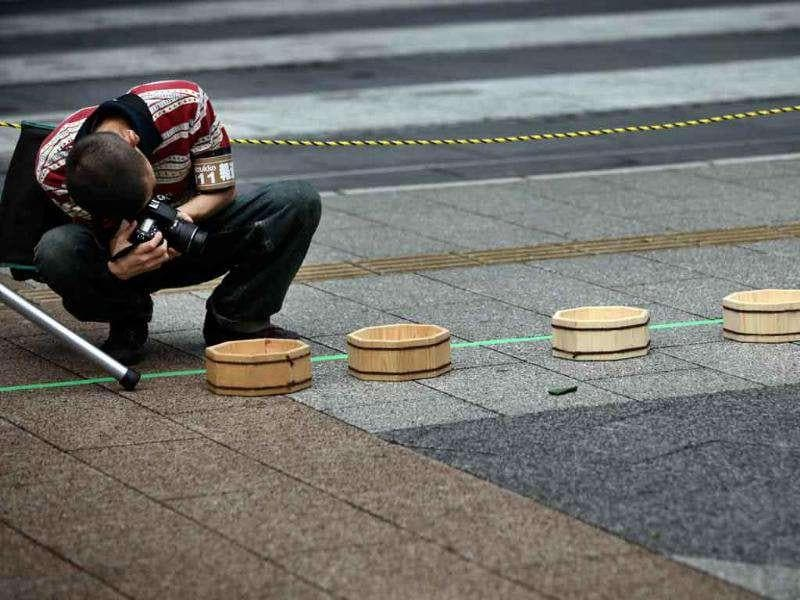 A man shoots wooden buckets placed on the ground before a promotional event to begin in Tokyo.