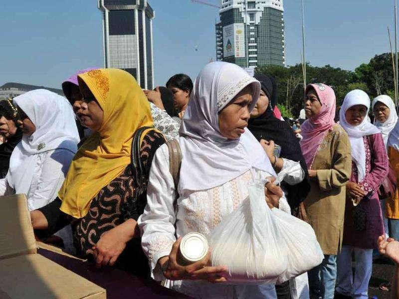 Indonesians queue to buy subsidized groceries a day before the month of Ramadan.