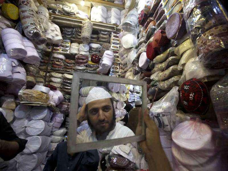 A Pakistani Muslim buys a traditional cap at a shop as he prepares for the upcoming Ramadan in Peshawar, Pakistan.