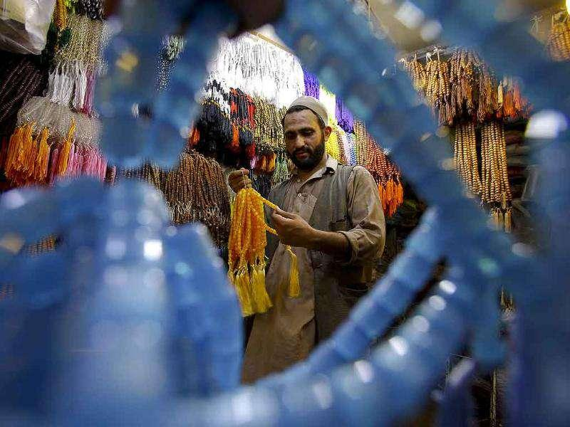 A Pakistani Muslim chooses prayer beads for the holy month of Ramadan, at a shop in Peshawar, Pakistan.
