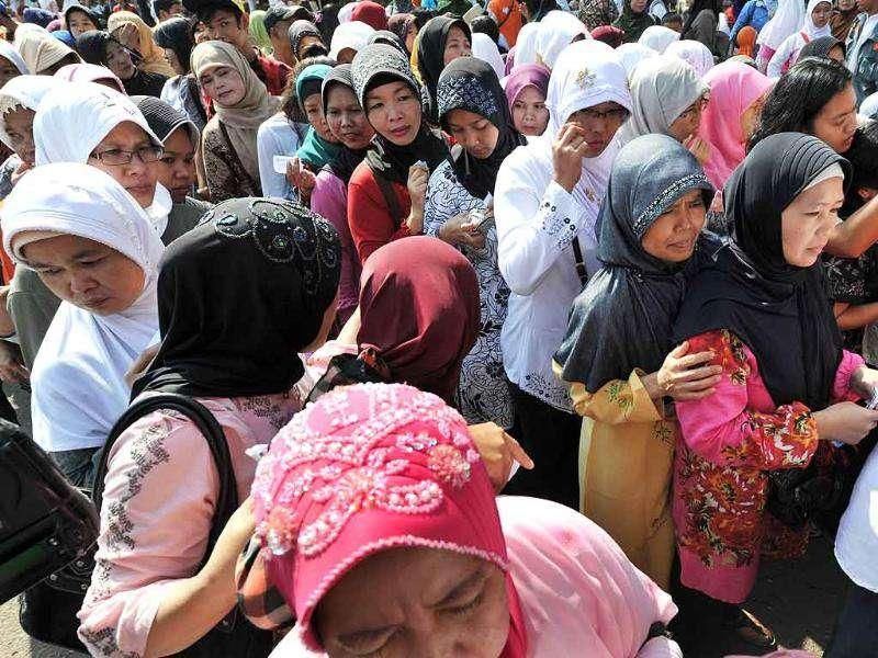 Indonesians queue to buy subsidized groceries a day before the month of Ramadan in Jakarta.