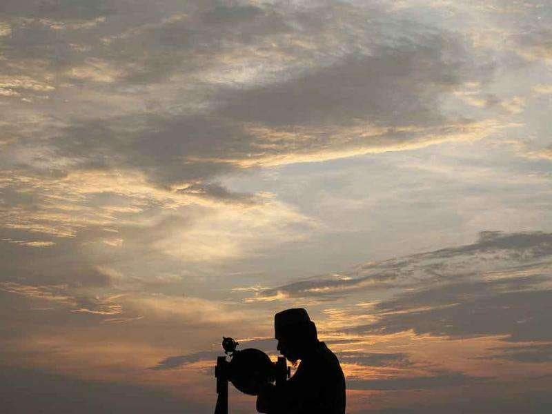 An officer of Malaysia's Islamic authority uses a telescope to perform