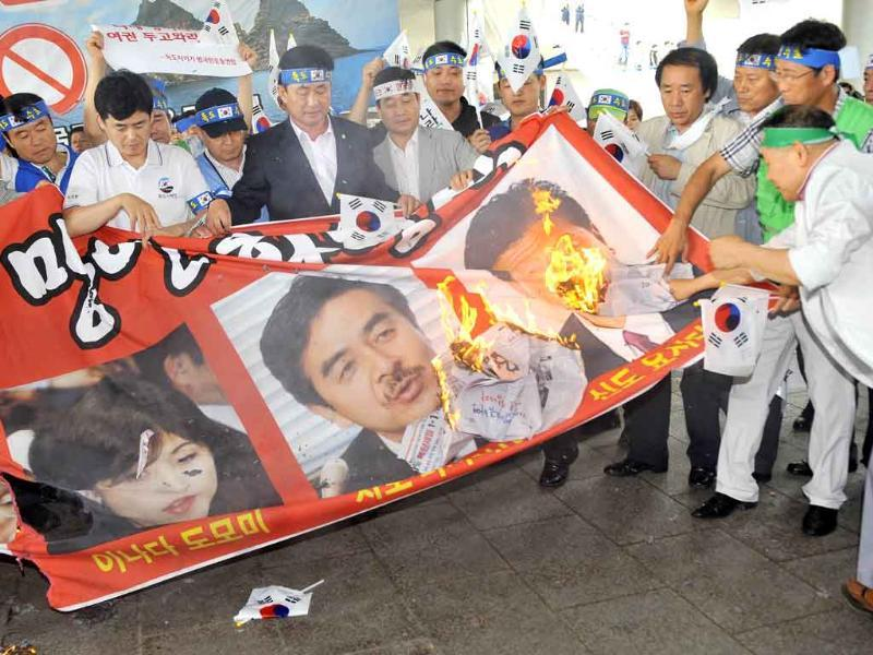 South Korean protesters burn a banner showing portraits of Yoshitaka Shindo (R), Domomi Inada (L) and Masahisa Sato (C), all from Japan's conservative Liberal Democratic Party, ahead of their planned arrival at Gimpo airport in Seoul.