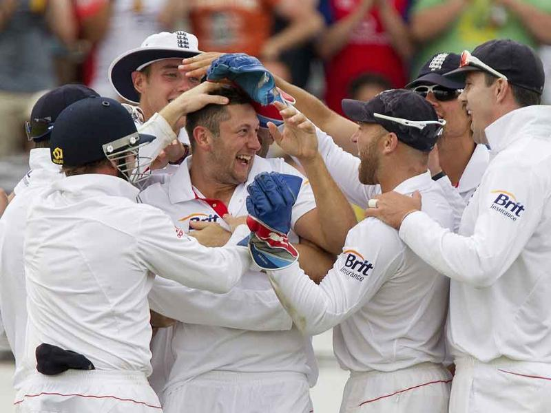 England's Tim Bresnan celebrates taking the wicket of Suresh Raina with Andrew Strauss and Graeme Swann during the fourth day of the second cricket Test match at Trent Bridge in Nottingham.