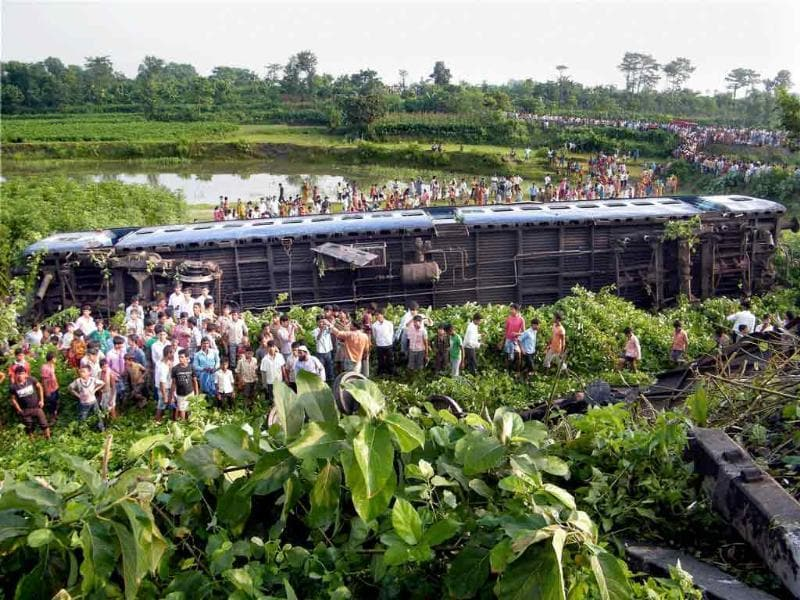 People watch damaged compartments of a train at the site of accident near Jamalghata railway station in Malda district on after a passenger train collided with Guwahati Bangalore express, previous day.