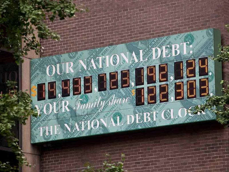 The National Debt Clock, a billboard-size digital display showing the increasing US debt, is seen on the corner of Sixth Avenue and West 44th Street in New York City. The House of Representatives successfully passed a bill that would reduce national debt and raise the national debt limit, though the bill still needs to pass the senate.