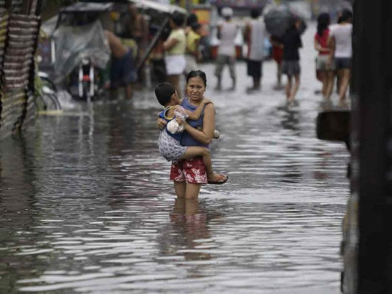 A Filipino boy holds on to his mother as they cross a flooded street brought by Typhoon Muifa in Manila, Philippines.