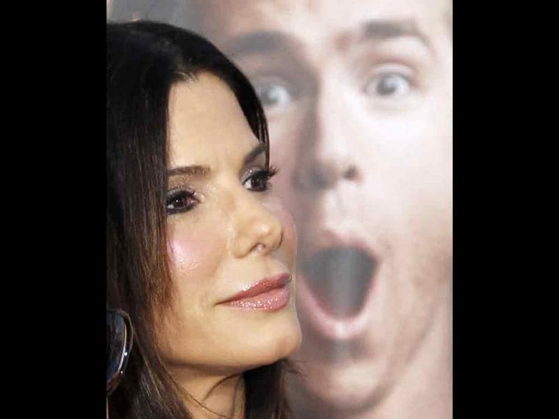 US actress Sandra Bullock walks past a poster of cast member Ryan Reynolds at the world premiere of the film The Change-Up in Los Angeles.