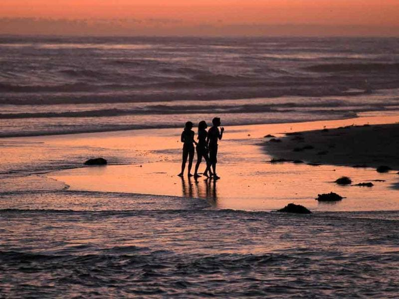 Children play along the shoreline after sunset in Cardiff, California.