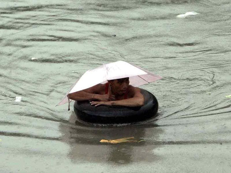 A man uses a floater as he negotiates a chest-deep flood water in suburban Quezon City, north of Manila, Philippines.