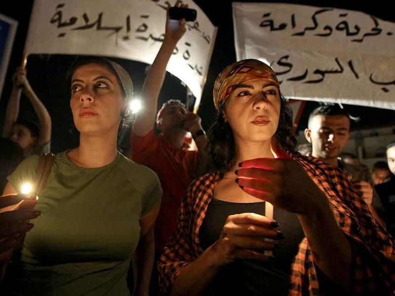 Women hold candles during a protest in front of the Syrian Embassy in Amman.
