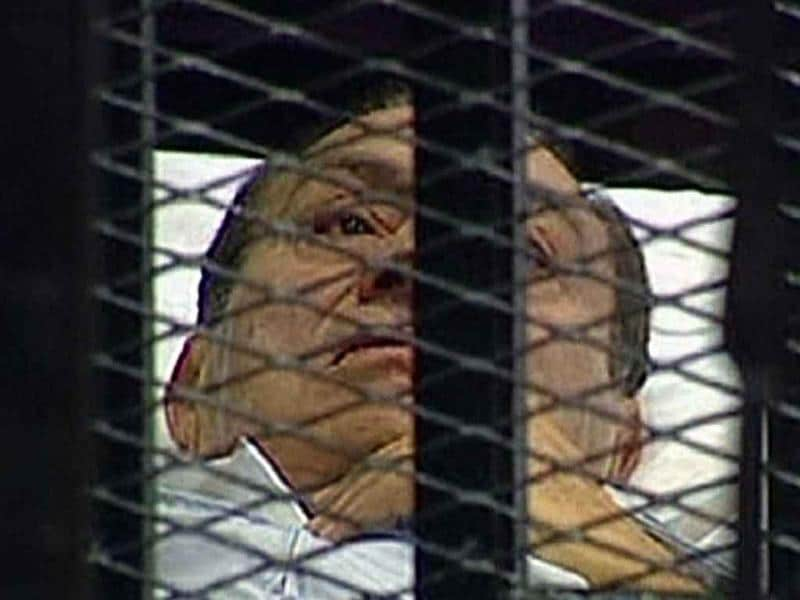 Egyptian former President Hosni Mubarak is wheeled into a holding cell in the court room in the police academy on the outskirt of the capital Cairo where he faces murder charges.
