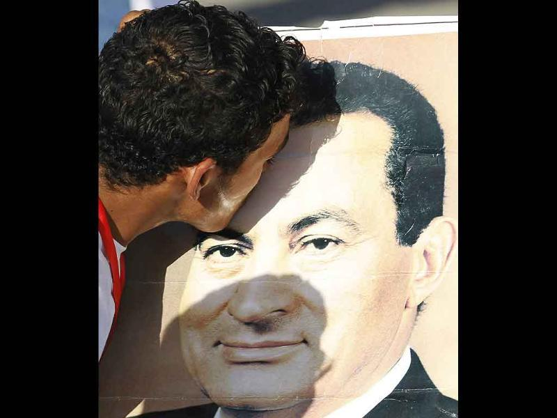 A supporter of former President Hosni Mubarak kisses a poster of him outside the police academy where his trial is taking place, in Cairo.