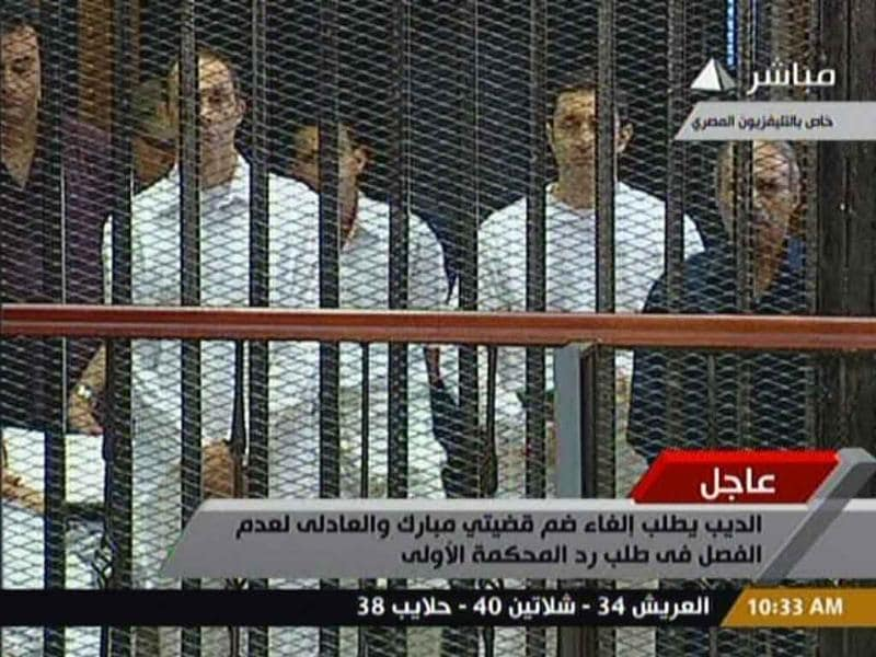 In this image taken from Egyptian State television on Wednesday, Egyptian former interior minister Habib al Adly stands along side Alaa and Gamal Mubarak in a holding cell in the court room in the police academy on the outskirt of the capital Cairo, waiting for the start of their trial along with ousted Egyptian president Hosni Mubarak.