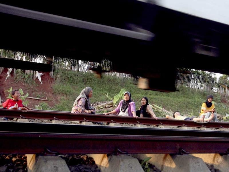 Villagers lie on a railway track for an electricity therapy in Rawa Buaya, Jakarta, Indonesia.