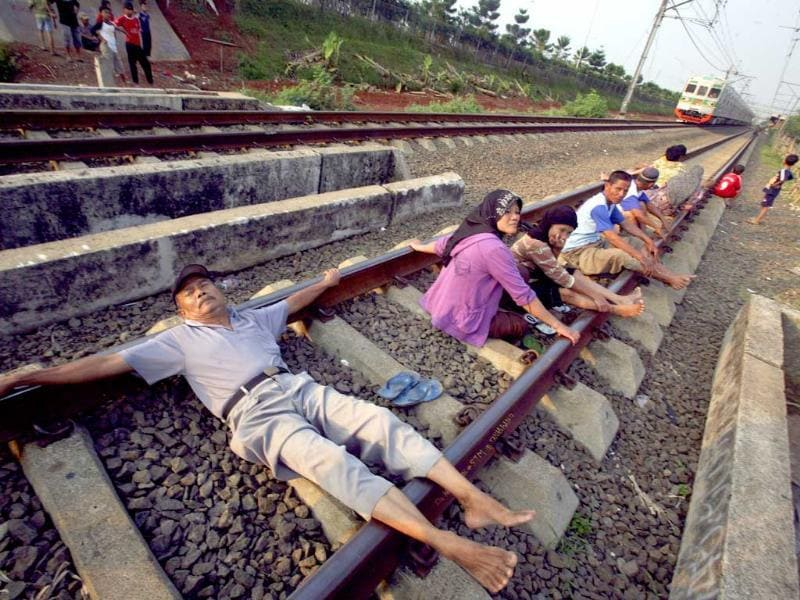 People lying on the railway track in Indonesia hoping to get cured by electric currents generated from the railway track.