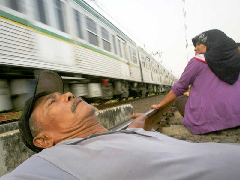 A train passes by as villagers hope to get cured by the electric current generated on the railway tracks in Indonesia.