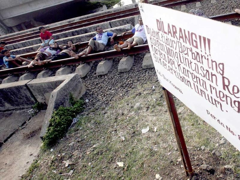 Villagers lie on a railway track for an electricity therapy near a sign put by local authority that says
