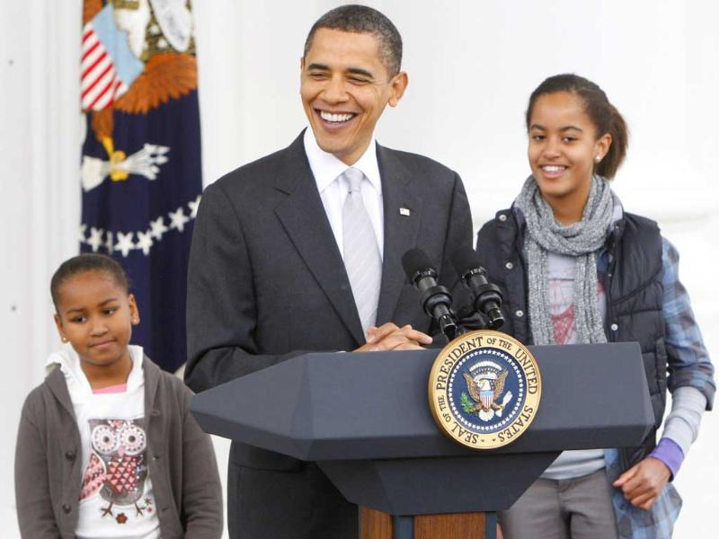 A file image of US President Brack Obama with daughters Malia and Sasha before pardoning the National Thanksgiving Turkey, Courage in a ceremony at the North Portico of the White House in Washington.