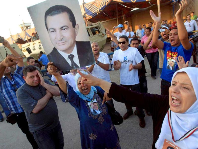 Supporters of ousted Egyptian president Hosni Mubarak hold his picture and shout slogans outside the police academy where Mubarak's trial is being held on the outskirt of Cairo. (AFP/Khaled Desouki)