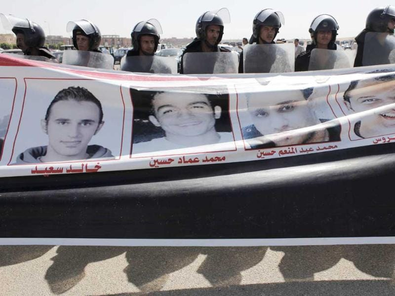 Egyptian riot police line up behind a banner with pictures of men killed during the revolution carried by anti-Mubarak protesters, outside the Police Military Academy complex in Cairo. (AP/Nasser Nasser)