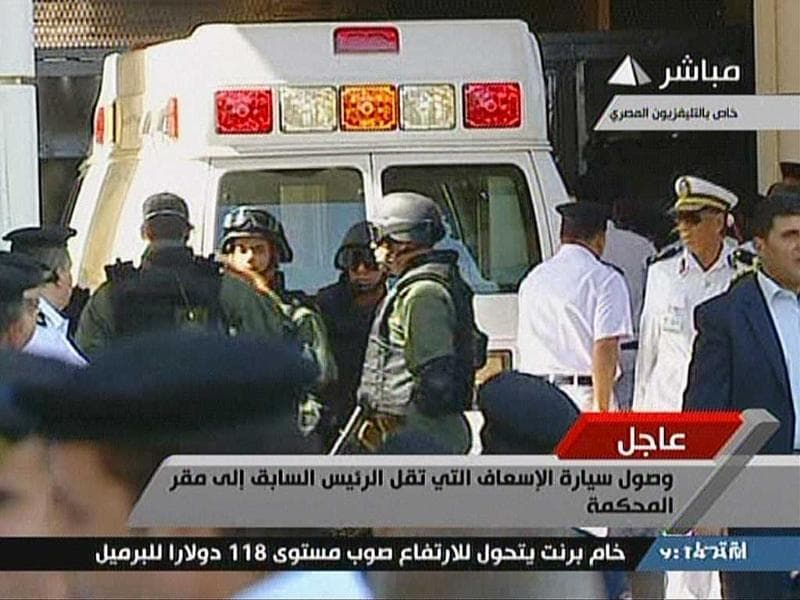 In this image taken from Egyptian State television, security stand by as a van beleived to be carrying the defendants arrives outside the court room set-up in the police academy. (AFP/Egyptian TV)