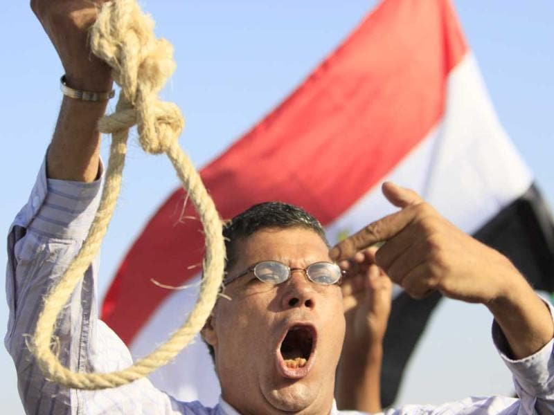 An Egyptian anti-Mubarak protester flashes a noose during a protest outside the police academy in Cairo. (AP/Amr Nabil)