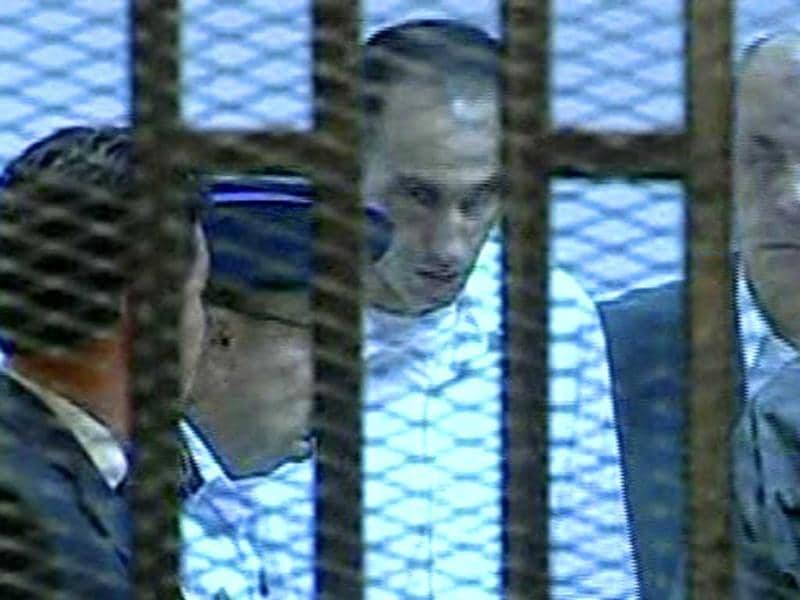 This video image taken from Egyptian State Television shows Hosni Mubarak's son Gamal, center in white, entering a cage of mesh and iron bars in a Cairo courtroom. (AP/Egyptian State TV)